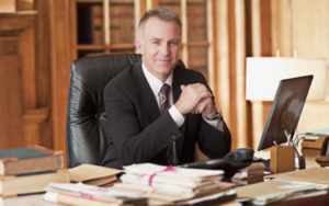 Smiling lawyer sitting at des